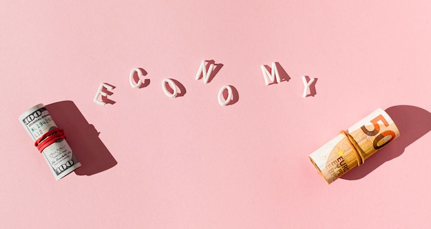 Рулоны банкнот с тенью и словом экономики