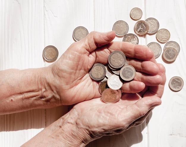 多くのユーロ硬貨のトップビューを持っている手
