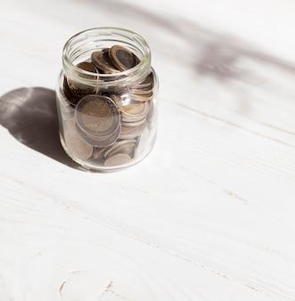白い背景の上のコインでいっぱいの瓶