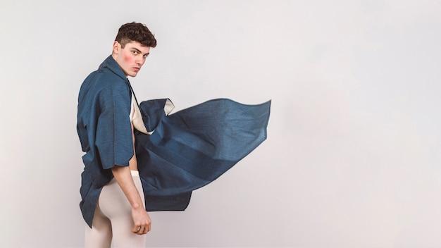 青い布でポーズの男