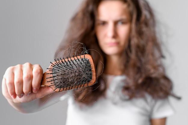 もつれた髪とブラシを持つ女性
