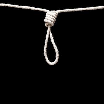 黒の背景に分離された絞首刑執行人の結び目の白いロープ