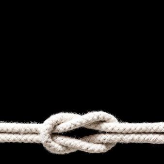 黒の背景に分離された白いロープの結び目を出荷します。