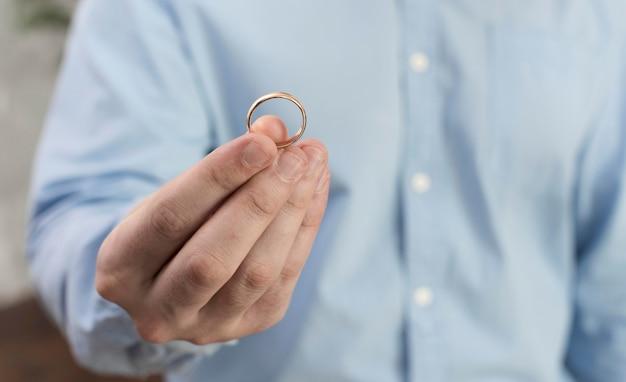 Крупным планом мужчина держит обручальное кольцо