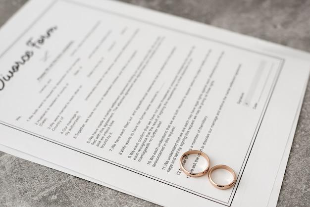 テーブルの上の結婚指輪とクローズアップの離婚フォーム
