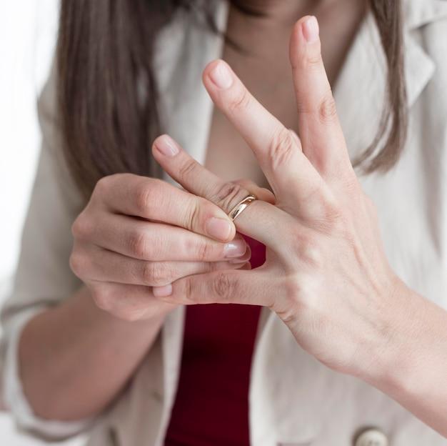 指から結婚指輪を取るクローズアップ女性
