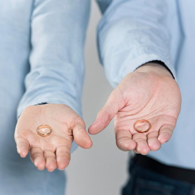 結婚指輪を保持しているクローズアップのカップル