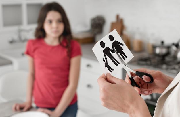 Крупным планом женщина резки семьи бумаги ножницами