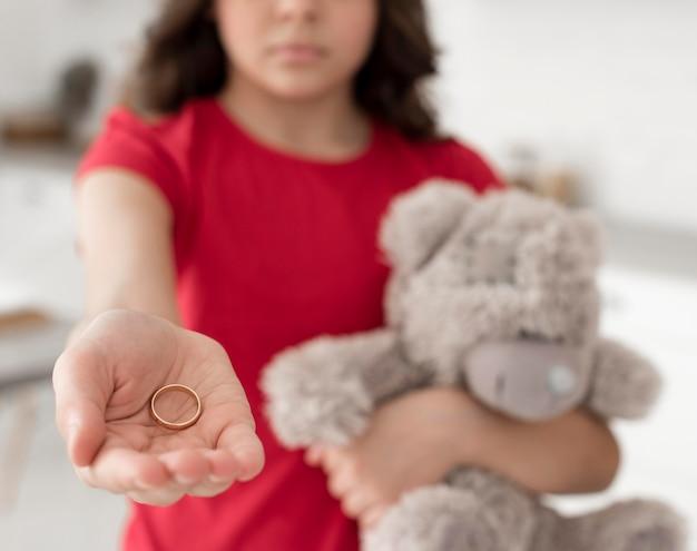 結婚指輪を保持しているクローズアップの若い女の子