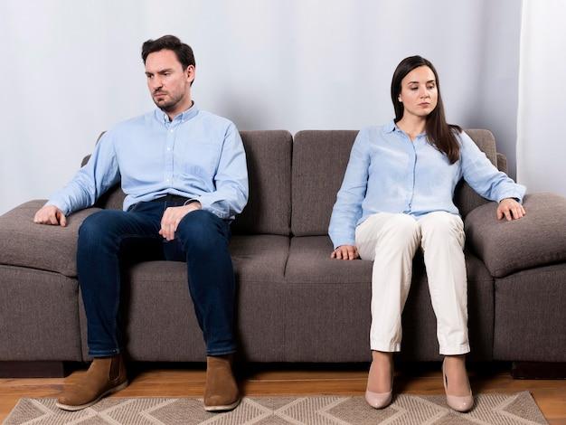 怒っている男性と女性がソファに座って