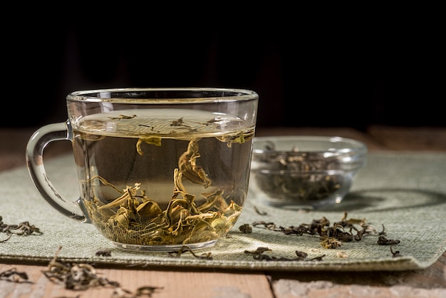 机の上のお茶のハーブとカップ