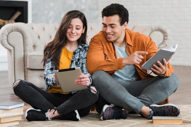 Пара читает книгу и из планшета
