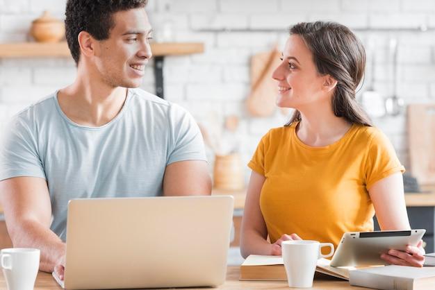 ノートパソコンとタブレットとキッチンに座っているカップル