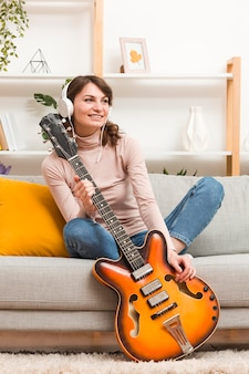 Женщина с наушниками держит гитару