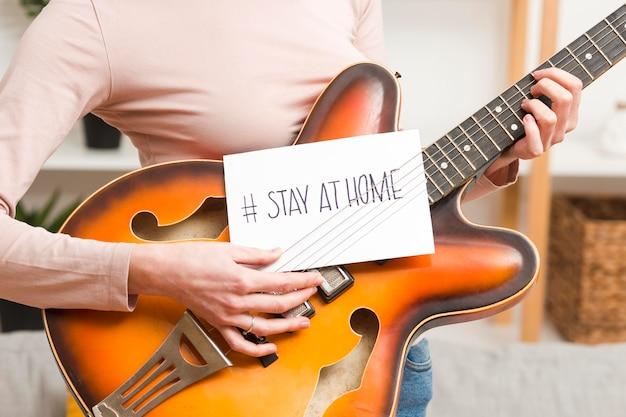 Крупным планом женщина на диване с гитарой