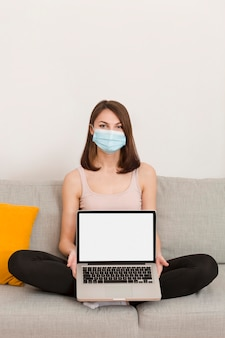 ノートパソコンとソファの上の肖像画の女性