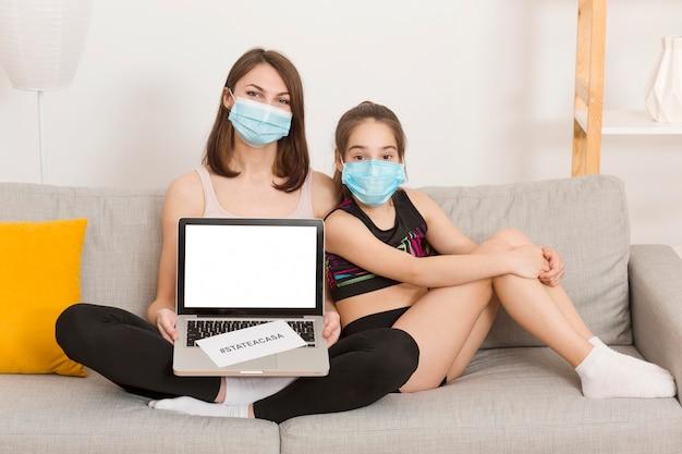 ママとソファの上の少女のラップトップ