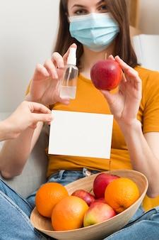 Женщина с дезинфицирующим средством и фруктами