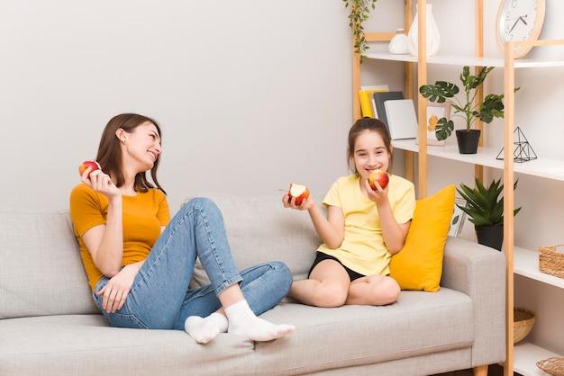 ママと女の子が果物を食べる