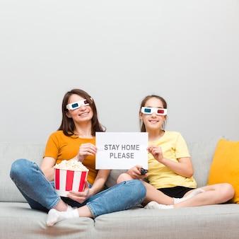 女の子とお母さんが家で映画を見て