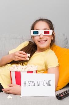 Молодая девушка на диване ест попкорн