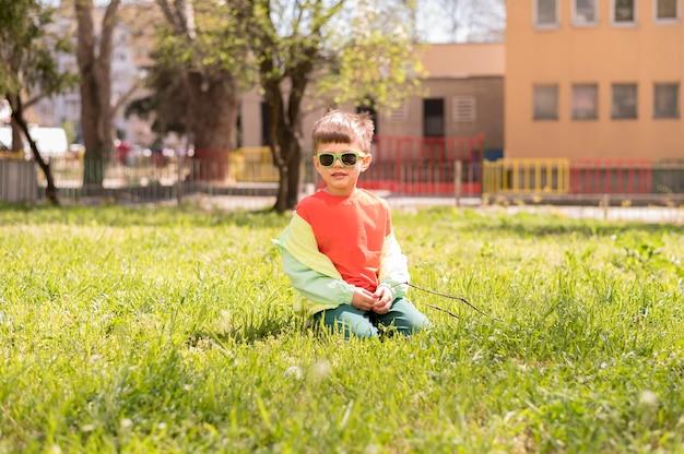 Маленький мальчик сидел в траве