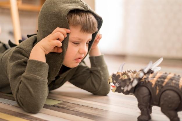 Боковой вид мальчик играет с динозавром