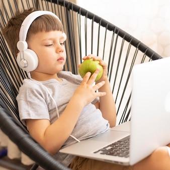ヘッドフォンとラップトップ食用リンゴを持つ少年