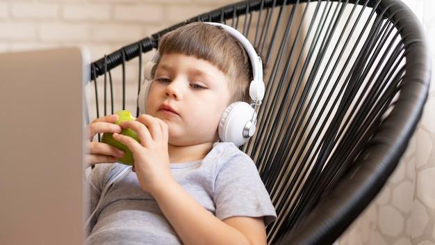椅子の食用リンゴにヘッドフォンを持つ少年