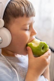 ヘッドフォン食用リンゴの小さな男の子