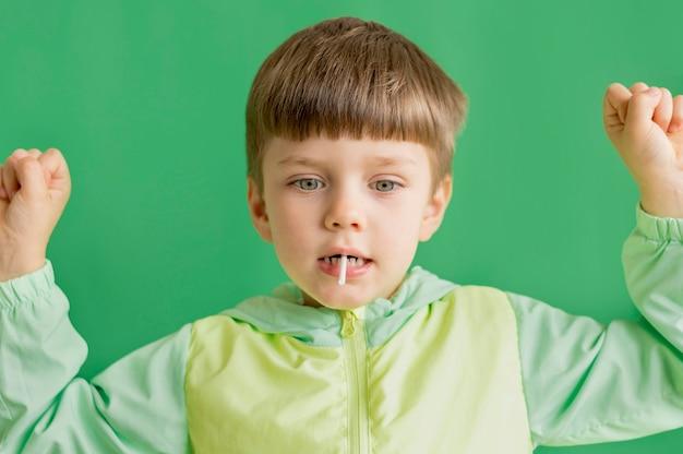 ロリポップを食べる正面少年