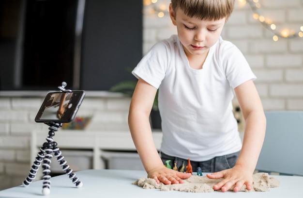 Средний выстрел ребенок играет с песком