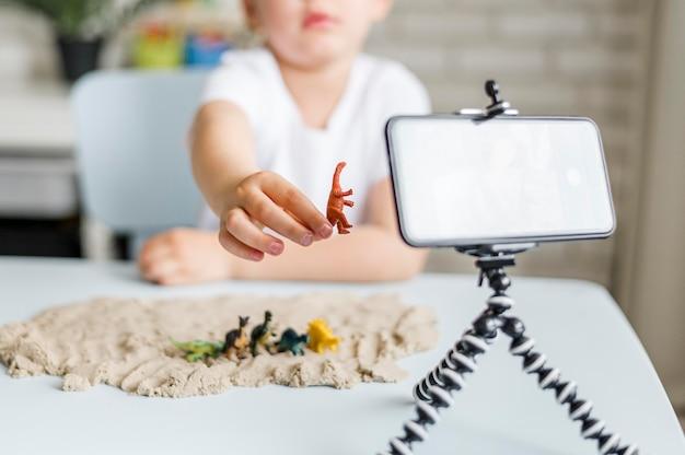 Крупным планом ребенок держит динозавра