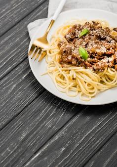 Тарелка с спагетии болоньезе и столовыми приборами