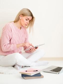 Женщина сидит на кровати и учится