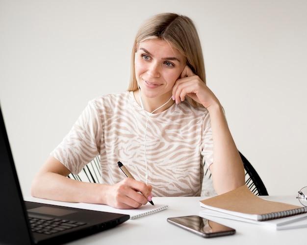 Женщина вид спереди, сидя на своем домашнем столе