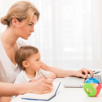 半ばショット深刻な母親持株赤ちゃんのデスクでの作業