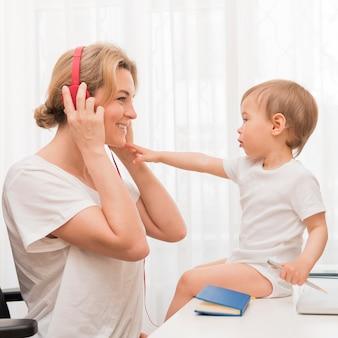 ヘッドフォンと机の上の赤ちゃんを持つ母親を閉じる