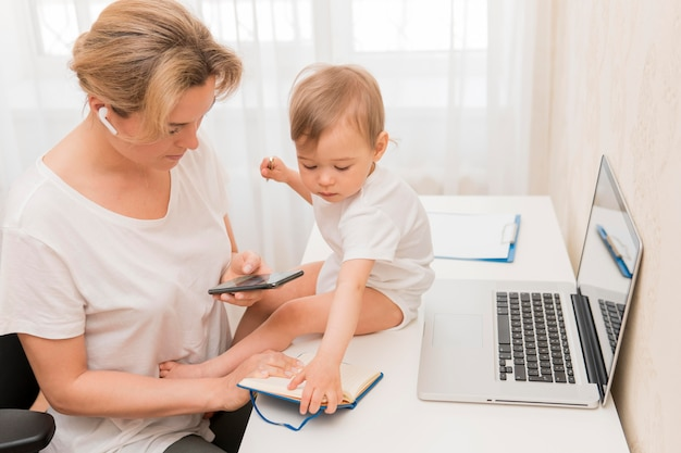 電話と机の上の赤ちゃんを見てハイアングルの母