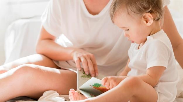 ママと赤ちゃんの本が付いているベッドに座っています。