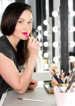 赤い口紅を適用する女性