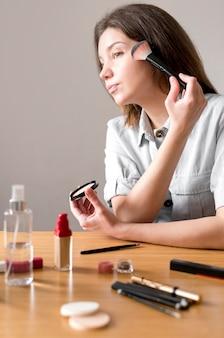 赤面を適用する若い女性
