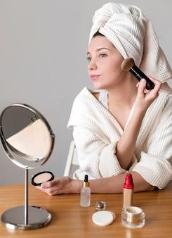 赤面を適用する低角度の女性