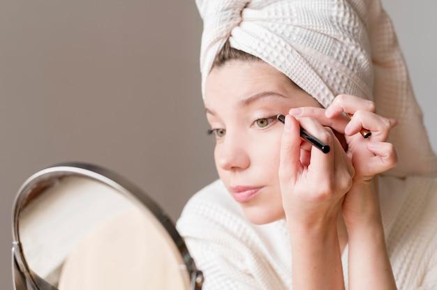 鏡にアイライナーを適用する女性