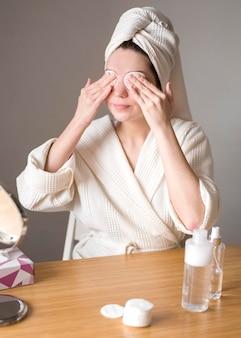 ミセル水でアイシャドウを取り除く女性