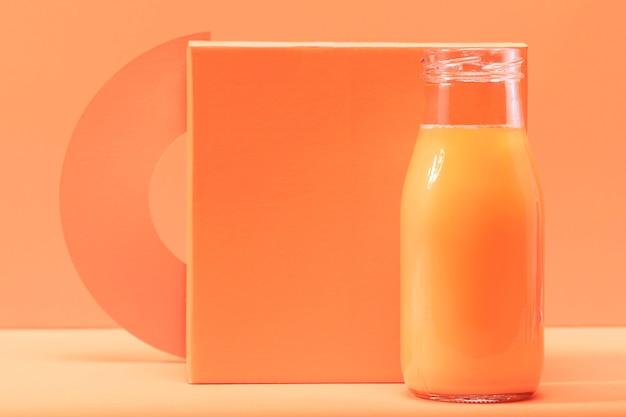オレンジ色の正方形の前にボトルに入った正面スムージー