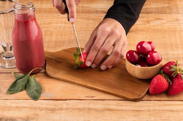 Человек под большим углом срезает фрукты рядом со смузи