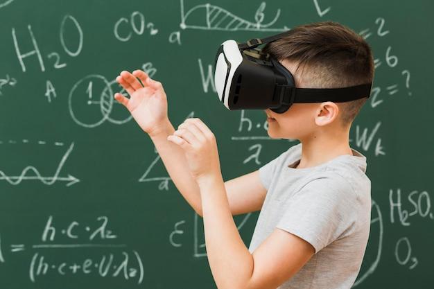 Вид сбоку мальчика с помощью гарнитуры виртуальной реальности