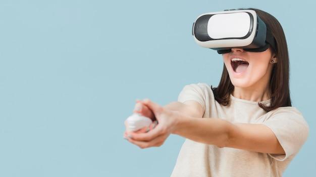 Женщина с удовольствием во время игры с гарнитурой виртуальной реальности