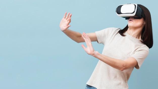 Женщина, наслаждаясь ее время при использовании гарнитуры виртуальной реальности